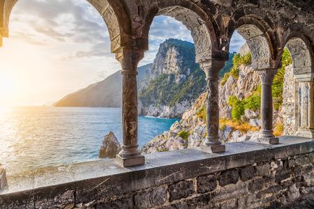 Kolommen van de beroemde gotische kerk van St. Peter (Chiesa di San Pietro) met prachtige kustlijn landschap bij zonsondergang in de stad Porto Venere, Ligurische kust, provincie La Spezia, Italië