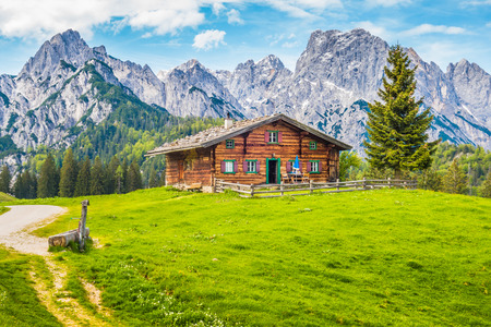 Panoramic view of scenic mountain landscape in the Alps with traditional old mountain chalet and fresh green meadows on a sunny day with blue sky and clouds in spring