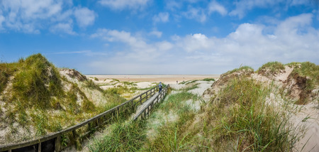 Idyllische pad in typisch Europees noordzee duinlandschap leidt naar het strand op een zonnige dag met mooie cloudscape