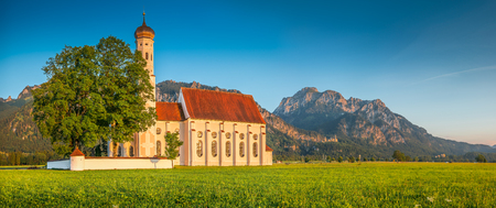 schwangau: Panoramic view of famous St. Coloman church with scenic Neuschwanstein Castle in the background in beautiful evening light at sunset in summer, Schwangau, Fussen, Bavaria, Germany