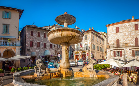 figuring: Beautiful panoramic view of famous Piazza del Comune with historic fountain figuring three lions and ancient palaces in the background on the main sqaure of Assisi, Umbria, Italy