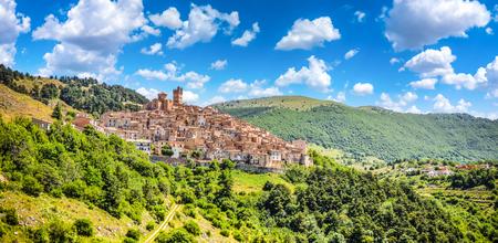 Beautiful view of idyllic village Castel del Monte, set into a steep hillside under apennine mountain peaks on a sunny summer day, Gran Sasso e Monti della Laga National Park, LAquila, Abruzzo, Italy