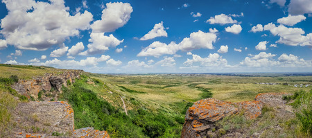 Beautiful aerial view of Canadian Prairie at Head-Smashed-In Buffalo Jump  in Southern Alberta on a sunny day with blue sky and clouds in summer, Canada