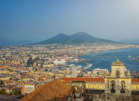 Napoli: Scenic picture-postcard view of the city of Napoli (Naples) with famous Mount Vesuvius in the background in golden evening light at sunset, Campania, Italy