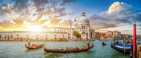 venice: Beautiful view of traditional Gondolas on famous Canal Grande with historic Basilica di Santa Maria della Salute in the background in romantic golden evening light at sunset in Venice, Italy Stock Photo