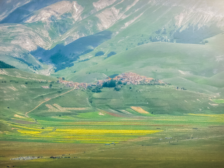 sibillini: Famous mountain village of Castelluccio di Norcia with beautiful summer landscape at Piano Grande (Great Plain) mountain plateau in the Apennine Mountains on a sunny summer day, Umbria, Italy