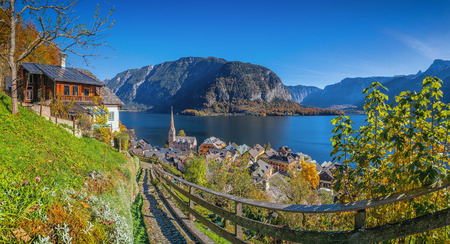 austrian village: Scenic picture-postcard view of idyllic Hallstatt mountain village with famous lake Hallstatter See in the Austrian Alps on a beautiful sunny day with blue sky in fall, region of Salzkammergut, Austria