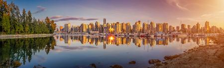 美しいバンクーバーのスカイラインと夏には、ブリティッシュ コロンビア州、カナダで日没で牧歌的な夜の光でスタンレー公園から有名な港エリア