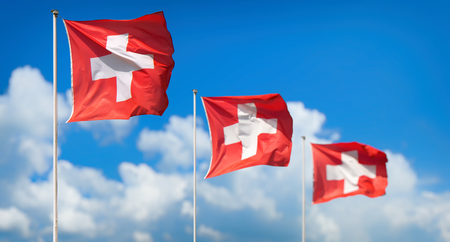 panorama view: Panorama view of three national flags of Switzerland waving in the sunshine against blue sky and clouds at First of August, the national holiday of the Swiss Confederation Stock Photo
