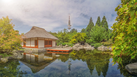 teahouse: Beautiful view of Japanese Garden in Planten un Blomen park with famous Heinrich-Hertz-Turm radio telecommunication tower in the background on a sunny day with blow sky in summer, Hamburg, Germany