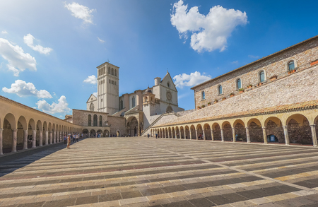 Beautiful view of famous Basilica of St. Francis of Assisi (Basilica Papale di San Francesco) with historic Lower Plaza on a sunny day with blue sky and clouds, Assisi, Umbria, Italy Stock Photo