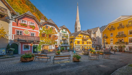 Scenic picture-postcard view of the historic town square of Hallstatt with traditional colorful houses and church at Hallstatter See in the Austrian Alps in fall, region of Salzkammergut, Austria