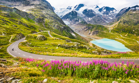 Beautiful view of motorcyclist driving on winding mountain pass road in the Alps through gorgeous scenery with mountain peaks, glaciers, lakes and green pastures with blooming flowers in summer