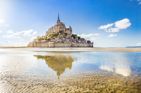 Panoramic view of famous Le Mont Saint-Michel tidal island on a sunny day with blue sky and clouds, Normandy, northern France Standard-Bild
