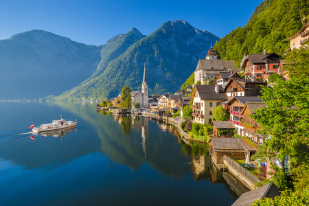 Scenic picture-postcard view of famous Hallstatt mountain village in the Austrian Alps with passenger ship in beautiful morning light on a sunny day in summer, Salzkammergut region, Austria