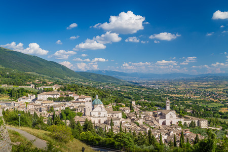 of assisi: Panoramic view of the historic town of Assisi on a beautiful sunny day with blue sky and clouds in summer, Umbria, Italy