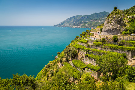 Panoramic picture-postcard view of famous Amalfi Coast with vineyards and Gulf of Salerno on a sunny day with blue sky in summer, Campania, Italy