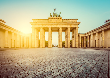 mauer: Famous Brandenburger Tor (Brandenburg Gate), one of the best-known landmarks and national symbols of Germany, in beautiful golden morning light at sunrise with lens flare effect, Berlin, Germany