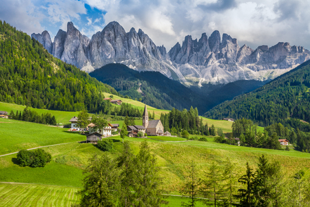 Beautiful view of idyllic mountain scenery in the Dolomites with famous Santa Maddelana mountain village on a sunny day with blue sky and clouds in spring, Val di Funes, South Tyrol, northern Italy