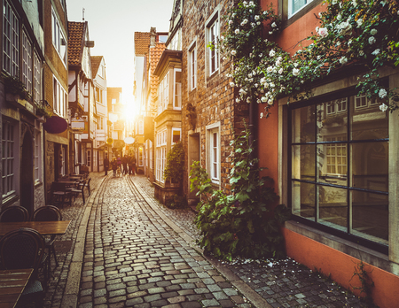 Mooi uitzicht op de oude stad in Europa in gouden avondlicht bij zonsondergang in de zomer met pastelkleurig retro vintage stijl grunge filter en lens flare zonlicht effect