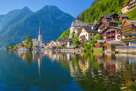 Scenic picture-postcard view of famous Hallstatt village reflecting in Hallstattersee lake in the Austrian Alps in beautiful morning light on a sunny day in summer, Salzkammergut region, Austria