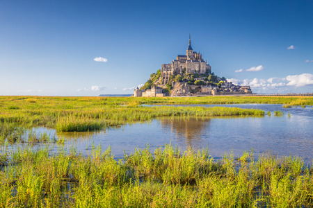 Classic view of famous historic Le Mont Saint-Michel tidal island on a sunny day with blue sky and clouds in summer, Normandy, northern France