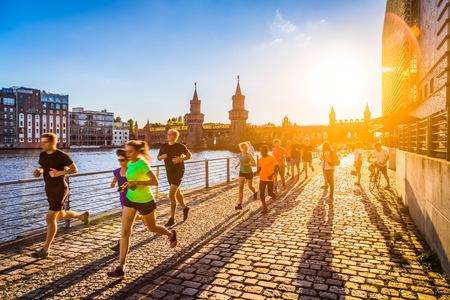 Groep van vrouwelijke en mannelijke jonge lopers joggen buiten in gouden avondlicht bij zonsondergang in de zomer met retro vintage stijl afgezwakt filter en lens flare zonlicht effect op de achtergrond