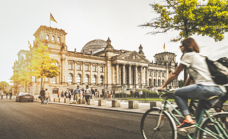Berlin urban city life with famous Reichstag building in the background in beautiful golden evening light at sunset in summer with retro vintage style pastel toned filter effect, Berlin, Germany Stock Photo