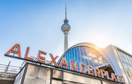 Wide-angle view of Alexanderplatz neon sign with famous TV tower and train station in golden evening light at sunset in summer, central Berlin Mitte district, Germany Editorial