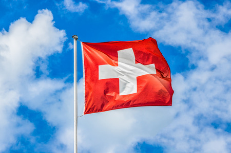 Classic view of the national flag of Switzerland waving in the wind against blue sky and clouds on a sunny day in summer on the First of August, the national holiday of the Swiss Confederation 版權商用圖片