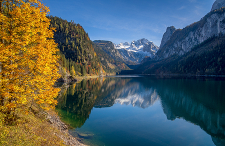 water fall: Beautiful view of idyllic colorful autumn scenery with Dachstein mountain summit reflecting in crystal clear Gosausee mountain lake in fall, Salzkammergut region, Upper Austria, Austria Stock Photo