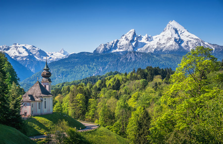 Beautiful panoramic view of snow-capped Watzmann mountain top with historic pilgrimage church Maria Gern on a sunny day with blue sky in springtime, Nationalpark Berchtesgadener Land, Bavaria, Germany