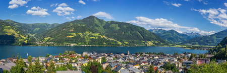 Panoramic view of beautiful mountain landscape in the Alps with the famous city of Zell am See and the idyllic Zeller Lake on a sunny day with clouds and blue sky in summer, Salzburger Land, Austria Stock Photo