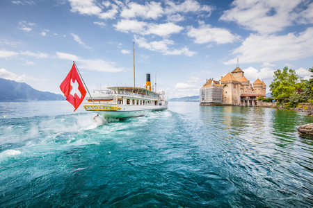Scenic panorama view of traditional paddle steamer excursion ship with historic Chateau de Chillon at famous Lake Geneva on a sunny day with blue sky and clouds in summer, Canton of Vaud, Switzerland