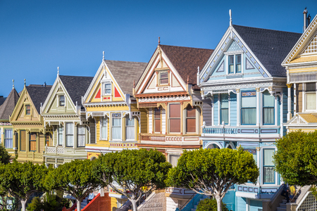 rowhouses: Classic postcard view of famous Painted Ladies, a row of colorful Victorian houses located near scenic Alamo Square, on a beautiful sunny day with blue sky in summer, San Francisco, California, USA