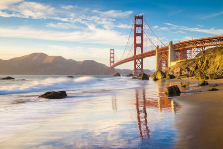 Klasyczny panoramiczny widok na słynny most Golden Gate widziany z malowniczej plaży Baker w pięknym złotym wieczornym świetle w słoneczny dzień z błękitnym niebem i chmurami latem, San Francisco, Kalifornia, USA Zdjęcie Seryjne