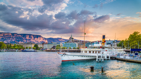 Panoramic view of the historic city center of Geneva with traditional paddle steamer boat on Lake Geneva in beautiful golden evening light at sunset with blue sky and clouds in summer, Switzerland 스톡 콘텐츠