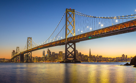 north gate: Classic panoramic view of famous Oakland Bay Bridge with the skyline of San Francisco illuminated in beautiful twilight after sunset in summer, California, USA