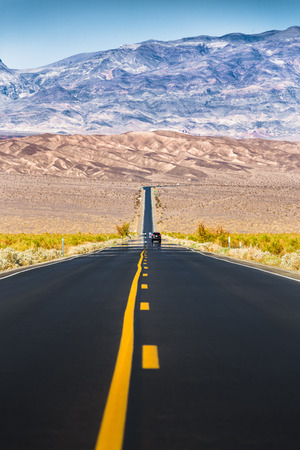 Classic vertical view of an endless straight road running through the barren scenery of famous Death Valley with extreme heat haze on a beautiful sunny day with blue sky in summer, California, USA Фото со стока