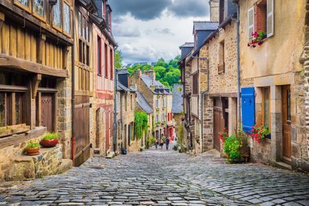Prachtig uitzicht op schilderachtig smalle steeg met historische traditionele huizen en geplaveide straat in een oude stad in Europa met blauwe hemel en wolken in de zomer met retro vintage grunge filter effect