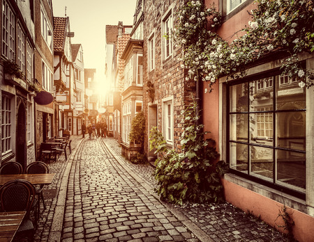 Beautiful view of old town in Europe in golden evening light at sunset in summer with pastel toned retro vintage  style grunge filter and lens flare sunlight effect
