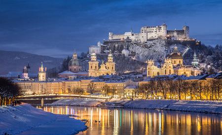 冬、ザルツブルク、オーストリアで風光明媚なクリスマスの時間の間に美しい夕暮れに照らされたホーエン ザルツブルク城とザルツブルクの有名な 写真素材