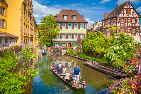 Beautiful view of the historic town of Colmar, also known as Little Venice, with tourists taking a boat ride along traditional colorful houses on idyllic river Lauch in summer, Colmar, Alsace, France Banco de Imagens