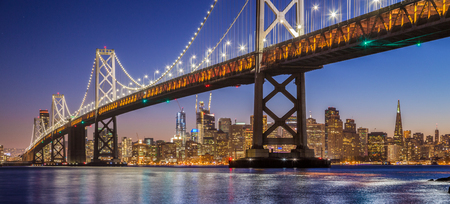 Classic panoramic view of famous Oakland Bay Bridge with the skyline of San Francisco illuminated in beautiful twilight after sunset in summer, California, USA 免版税图像 - 71043385
