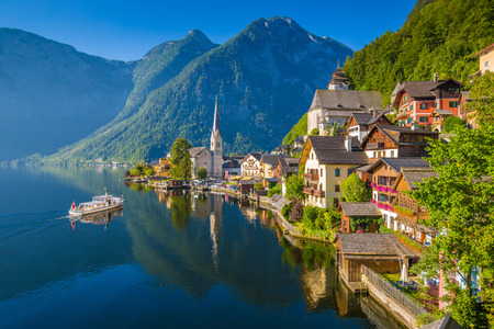 austrian village: Scenic picture-postcard view of famous Hallstatt mountain village in the Austrian Alps with passenger ship in beautiful morning light on a sunny day in summer, Salzkammergut region, Austria