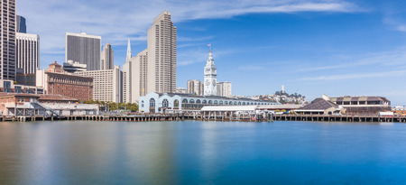 Panoramic view of San Francisco skyline with historic Ferry Building at famous Embarcadero street on a sunny day with blue sky and clouds in summer, California, USA Stock Photo
