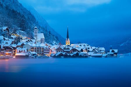 Vista postal clássica do cartão postal da famosa cidade Lakeside de Hallstatt nos Alpes no crepúsculo místico durante a hora azul ao amanhecer em um dia frio e nebuloso com nuvens no inverno, região de Salzkammergut, Áustria