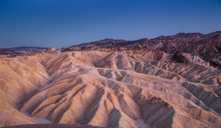 Scenic panoramic view of amazing sandstone formations at famous Zabriskie Point viewpoint in beautiful post sunset twilight, Death Valley National Park, California, USA Stock Photo