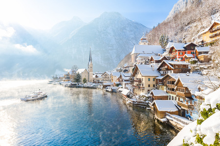Classic postcard view of famous Hallstatt lakeside town in the Alps with passenger ship on a beautiful cold sunny day with blue sky and clouds in winter, Salzkammergut region, Austria Reklamní fotografie - 71478839
