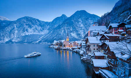 Classic postcard view of famous Hallstatt lakeside town in the Alps with traditional passenger ship on beautiful Hallstattersee in mystical twilight during blue hour in winter, Salzkammergut, Austria